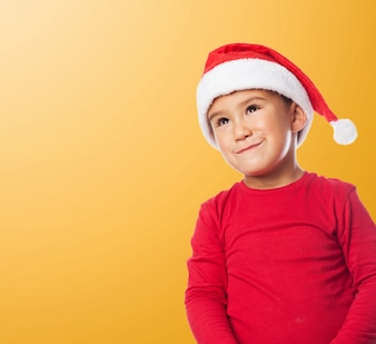 Забавный ребенок носить шляпу Санта с оранжевом фоне