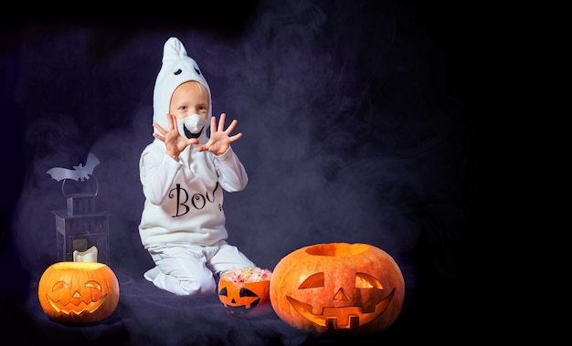 Funny child in a white carnival costume of a ghost in the room. boy playing with pumpkins and candy.