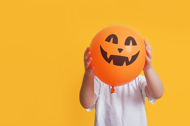 Funny child in a white t-shirt holding an orange balloon with a picture of jack lantern, halloween mock up, yellow background copy space