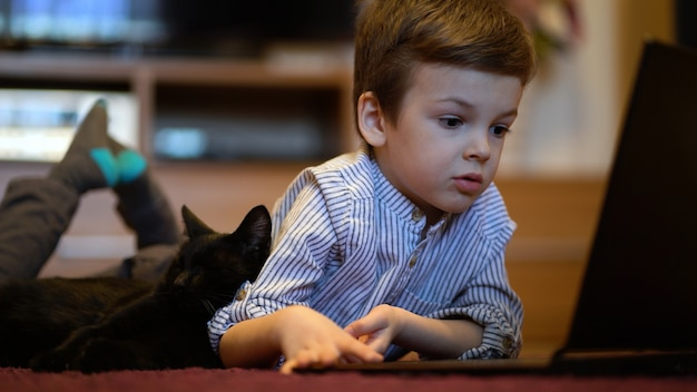 Funny child with kitten using a laptop at home