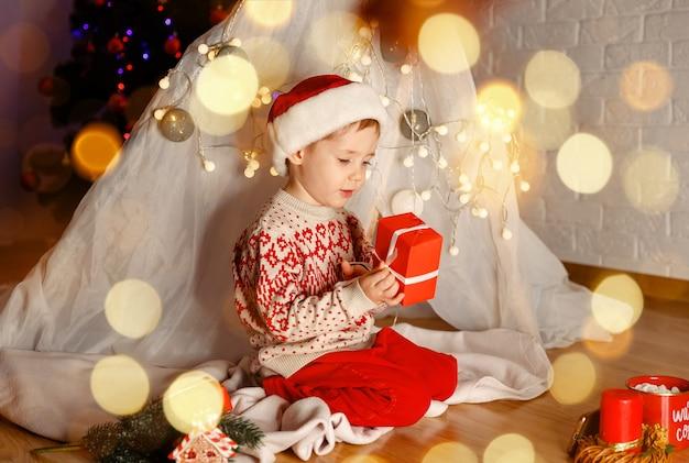 Забавный ребенок с волшебным подарком дома, семья, наслаждающаяся рождеством