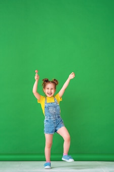 Funny child with raised hands in the air. girl with a lollipop is funny