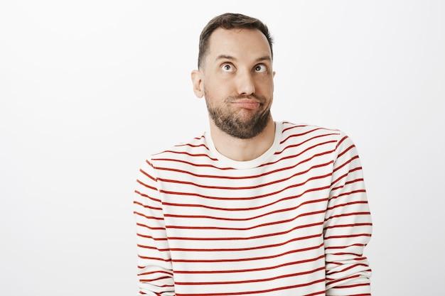 Забавный по-детски бородач в полосатом пуловере, корчит рожи или подражает, смотрит вверх прищуренными глазами и надувается