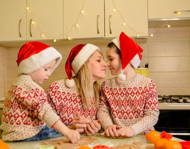 재미있는 아이들과 어머니는 크리스마스 쿠키를 굽습니다. 좋아하는 전통. 행복한 가족. 재미있는 아이들이 반죽을 준비하고 진저 브레드 쿠키를 굽고 있습니다.
