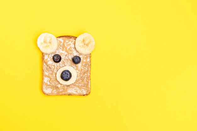 Funny children breakfast toast with peanut butter in a shape of bear with blueberry and banana. top view, copy space