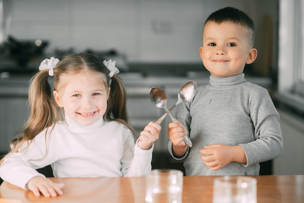 Funny children girl and boy in the kitchen with spoons, playing, going to eat cute