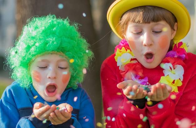 面白い子供たちの女の子は、カラフルな紙吹雪を笑顔で楽しんでカーニバルを祝います