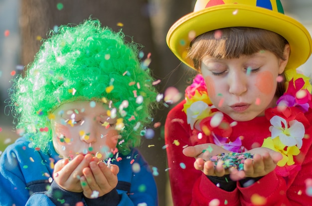 Funny children girls celebrate carnival smiling and having fun with  colorful confetti