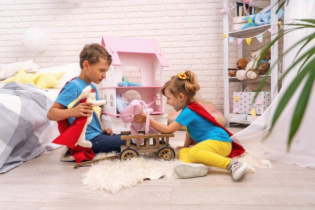 Funny children play with toys in the superheroes, in the children's room.