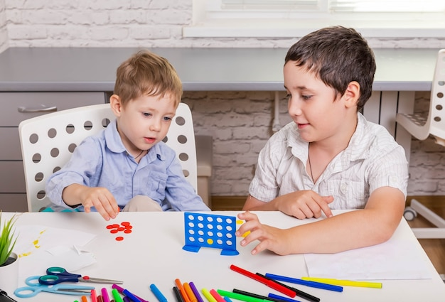 Funny children sitting on the chair and playing together board game at home