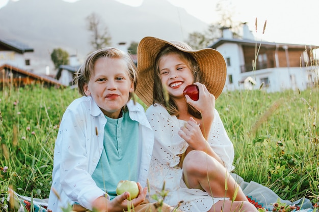 Funny children with apples brother and sister friends sitting in grass on background of village, rural scene