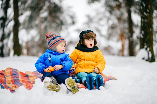 Funny children with expressive faces have winter party in snowy forest
