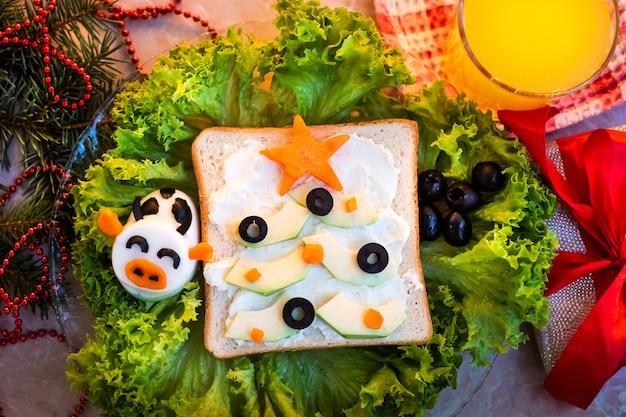面白いクリスマスの朝食、クリスマスツリーの形でサンドイッチ。アボカドの枝にオリーブとニンジンを添えて。フラットレイ、上面図、コピースペース。