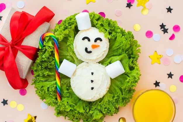 Funny christmas breakfast, sandwiches, snowman, rainbow candy, marshmallows.