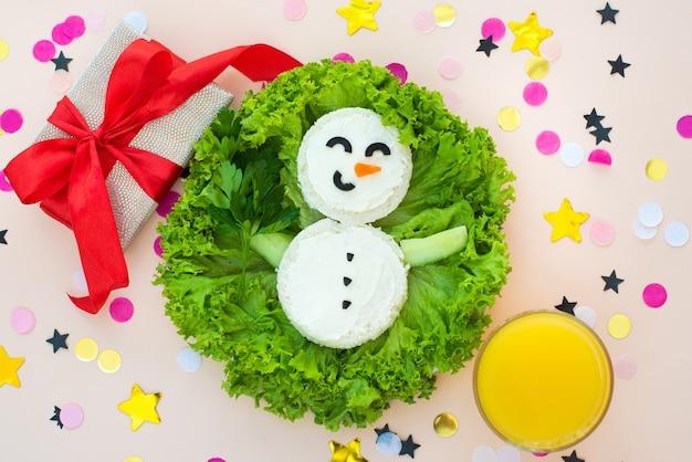 Забавный рождественский завтрак, бутерброды, снеговик с огурцом.