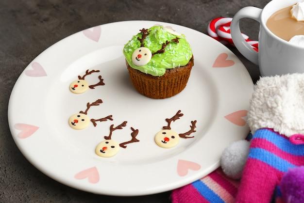 접시에 크림에서 재미 있는 크리스마스 컵 케이크와 사슴