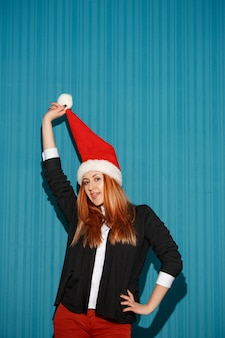 Funny christmas girl wearing a santa hat on the blue studio background