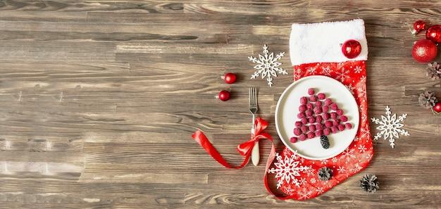 재미있는 크리스마스 트리 모양의 달콤한 신선한 라즈베리 베리는 어린이 어린이 아침 식사를 위해 나무 배경에 있는 접시에 있습니다. 새 해 장식으로 크리스마스 음식입니다. 배너 복사 공간입니다.