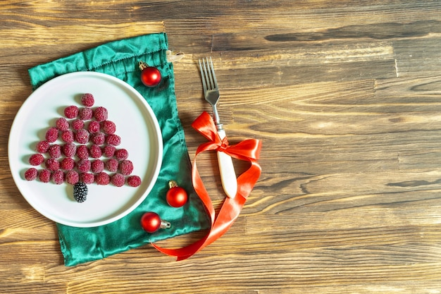재미있는 크리스마스 트리 모양의 달콤한 신선한 라즈베리 베리는 어린이 어린이 아침 식사를 위해 나무 배경에 있는 접시에 있습니다. 복사 공간이 있는 새해 장식이 있는 크리스마스 음식
