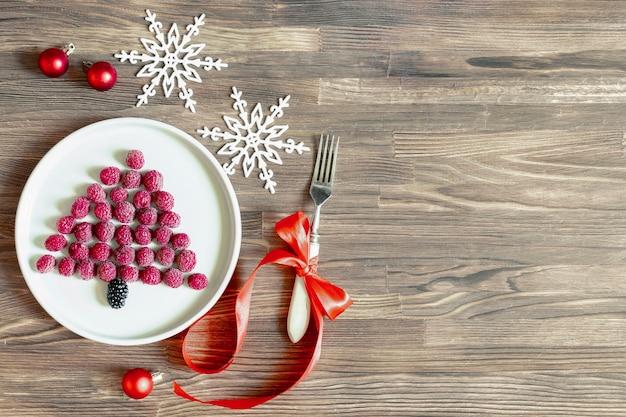 재미있는 크리스마스 트리 모양의 달콤한 신선한 라즈베리 베리는 어린이 어린이 아침 식사를 위해 나무 배경에 있는 접시에 있습니다. 복사 공간이 있는 새해 장식이 있는 크리스마스 음식.