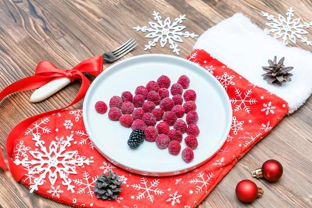 재미있는 크리스마스 트리 모양의 달콤한 신선한 라즈베리 베리는 어린이 어린이 아침 식사를 위해 나무 배경에 있는 접시에 있습니다. 새해 장식이 있는 크리스마스 음식