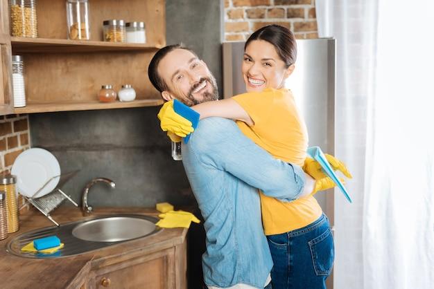 おかしい掃除。笑いながら掃除布を運んで抱き締める陽気なエネルギッシュな楽観的なカップル