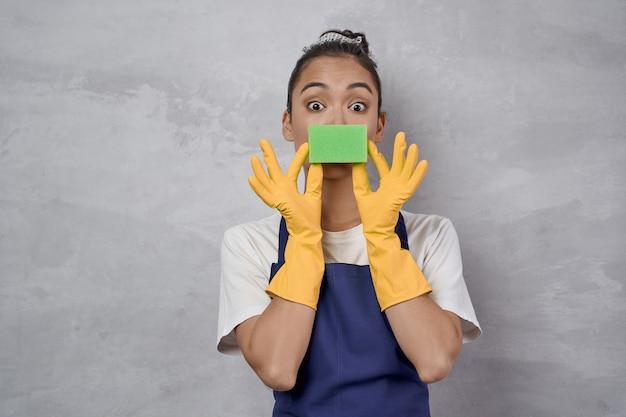 カメラを見ている台所のスポンジで遊んでいる制服とゴム手袋の面白い掃除婦