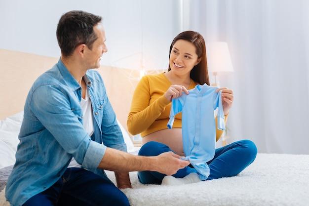 재미있는 옷. 남편을 바라보고 머리를 숙이는 동안 행복을 느끼는 매력적인 임신