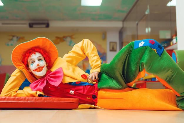 Funny clown in costume lying on the floor in children's area.
