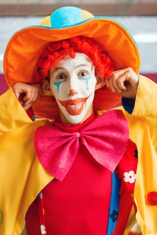 Funny clown dressed in colorful hat and costume