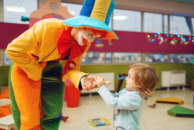 Funny clown gives out lollipop to happy little girl, friendship forever. birthday party  celebrating in playroom, baby holiday in playground.