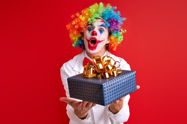 Funny clown holding gift box in hands posing isolated over red wall. celebration, game, children, performance concept
