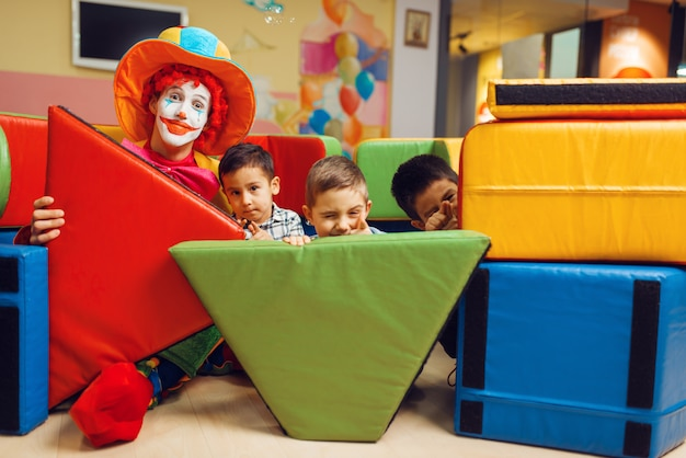 Funny clown and joyful little boys hid behind the soft blocks.