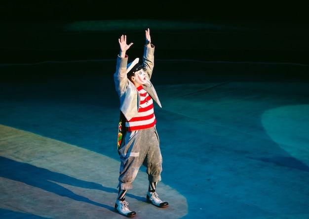 面白いピエロがサーカスで演奏します。