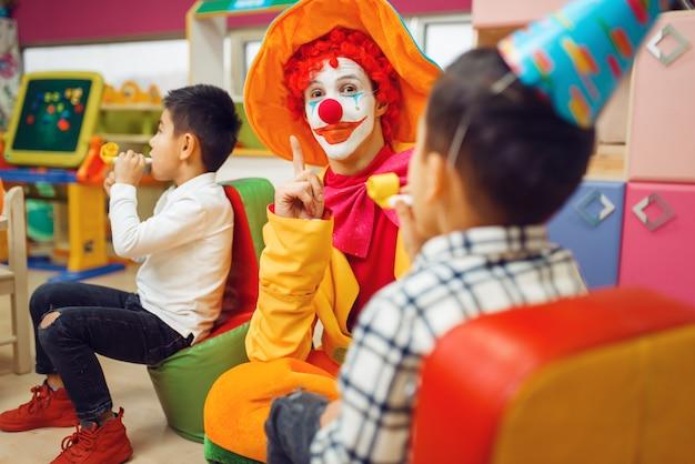 面白いピエロは一緒に陽気な子供たちと遊ぶ。プレイルームで祝う誕生日パーティー