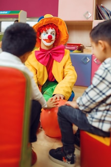 面白いピエロは一緒に陽気な子供たちと遊ぶ。