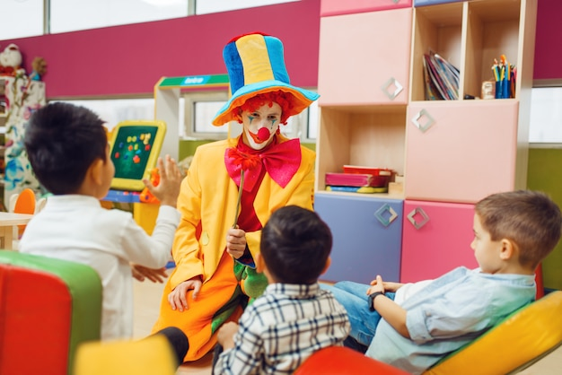 Funny clown play with cheerful children together