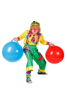 Funny clown with balls in studio isolated on white background