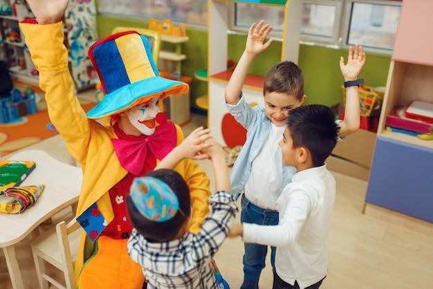 陽気な子供たちと一緒に面白いピエロは、一緒にカウントゲームをプレイします。プレイルームで祝う誕生日パーティー