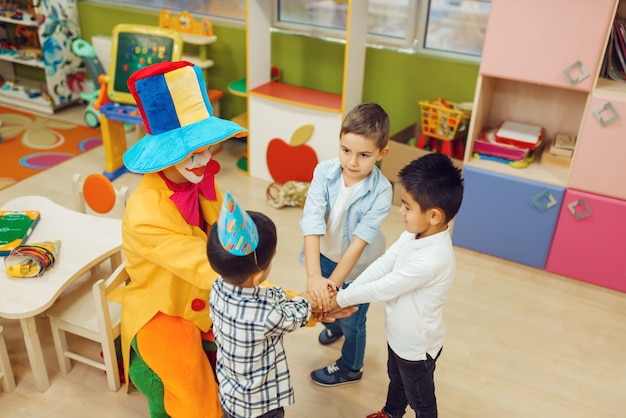Funny clown with cheerful children play counting game together.