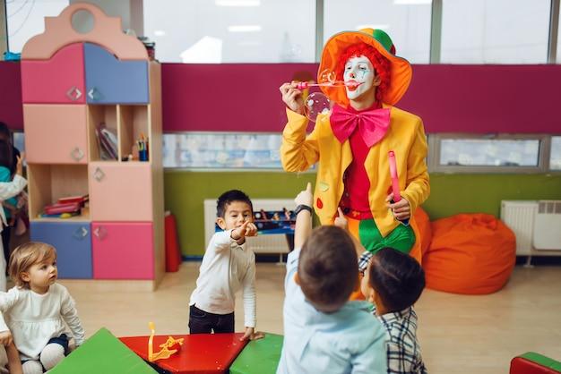 아이들과 함께 재미있는 광대는 비누 거품을 함께 팽창시킵니다.