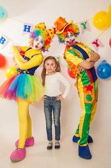 휴일에 재미있는 광대가 소녀와 좋은 감정을 보여줍니다.