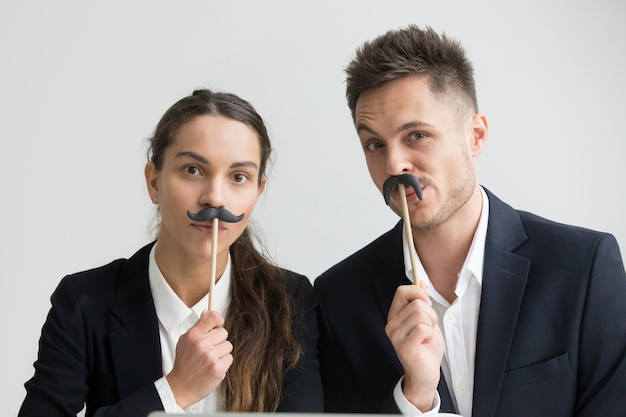 Funny colleagues making silly faces holding fake mustache, headshot portrait