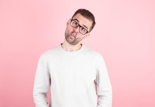 The funny comedian is crossing his eyes, fooling around after a day of school. goofy nerd with awkward facial expression having fun alone on pink