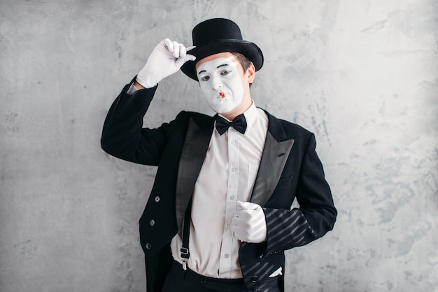 Funny comedy actor with makeup face. pantomime in suit, gloves and hat.