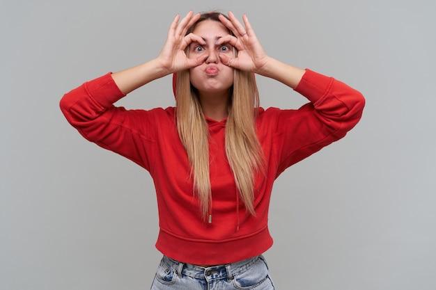 Giovane donna bionda comica divertente con le lentiggini in felpa con cappuccio rossa che fa gli occhiali con le mani e si diverte sul muro grigio