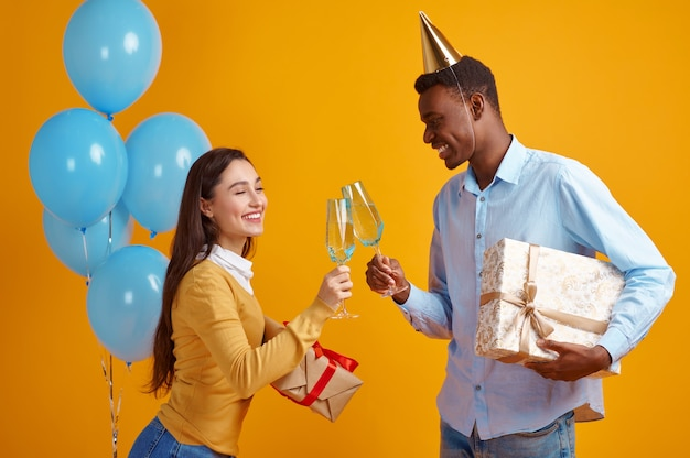 Funny couple in caps holding glasses of beverage and gift boxes. pretty female person got a surprise, event or birthday celebration, balloons decoration