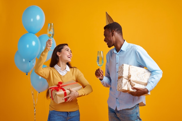 Funny couple in caps holding glasses of beverage and gift boxes, yellow background. pretty female person got a surprise, event or birthday celebration, balloons decoration