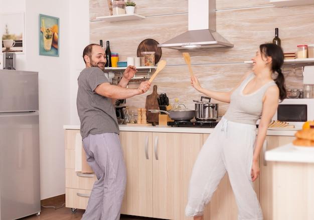 パジャマを着て朝食時にキッチンで踊る面白いカップル。のんきな妻と夫が笑って楽しんで面白い人生を楽しんでいる本物の既婚者ポジティブ幸せな関係