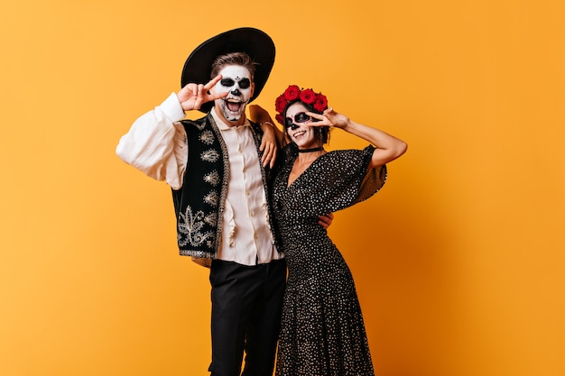 Funny couple in great mood posing on orange wall. portrait of man and woman with mexican-style face art showing peace sign.